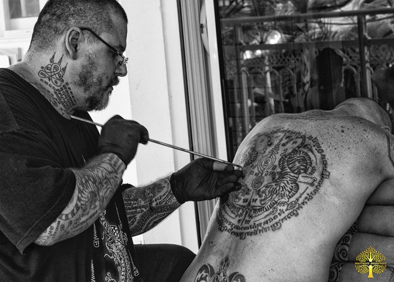 Ajarn Matthieu tattooing a follower with sua kru 2 facing tigers for practitioners of martial arts